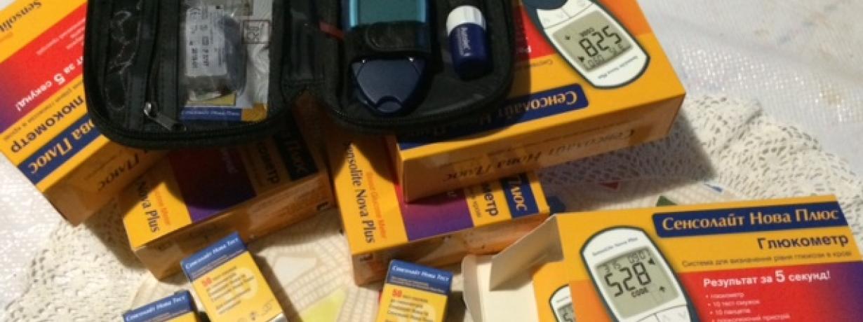Відкритий глюкометр на фоні упаковок з тестсмужками