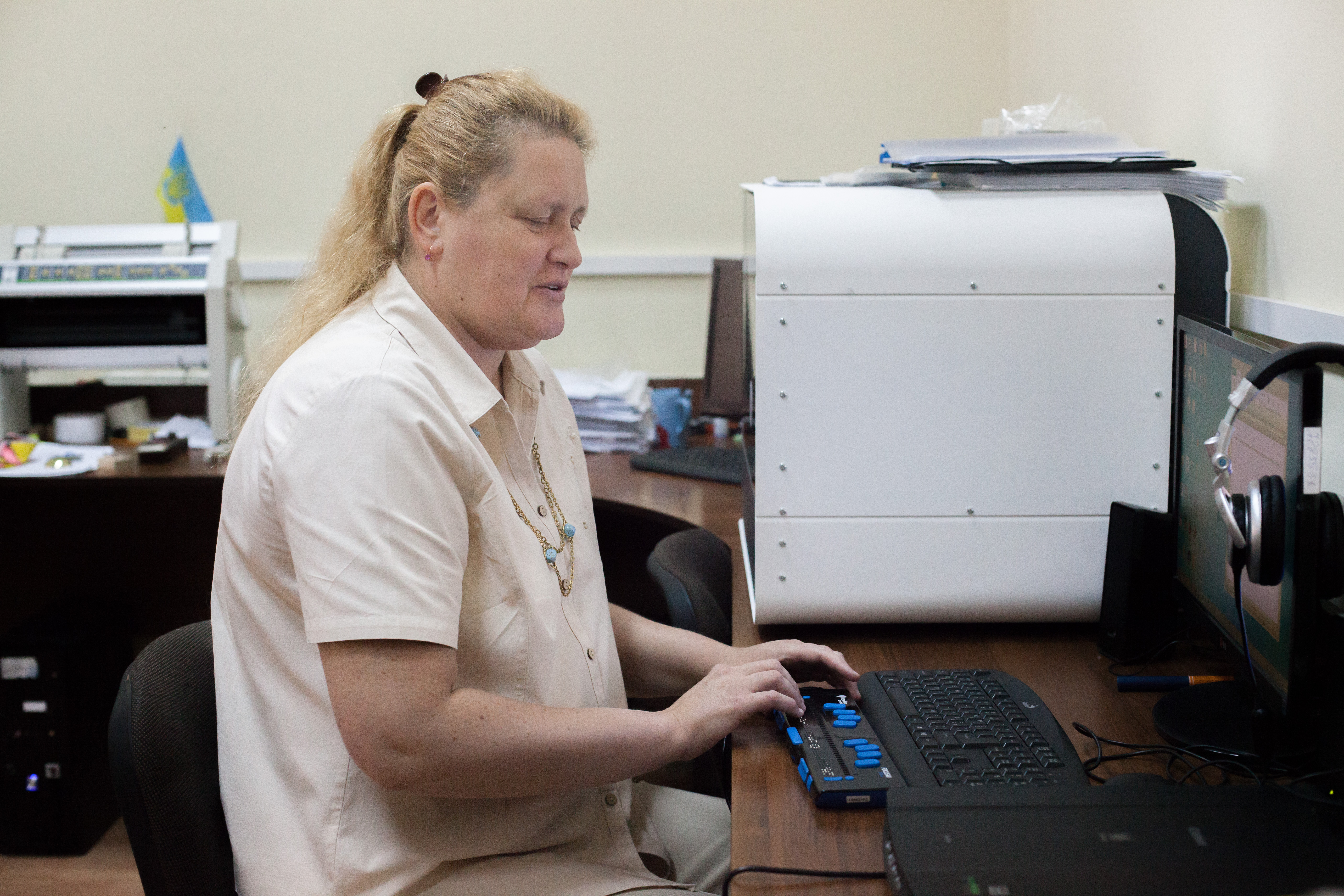 Оксана Потимко редагує текст на брайлівському дисплеї