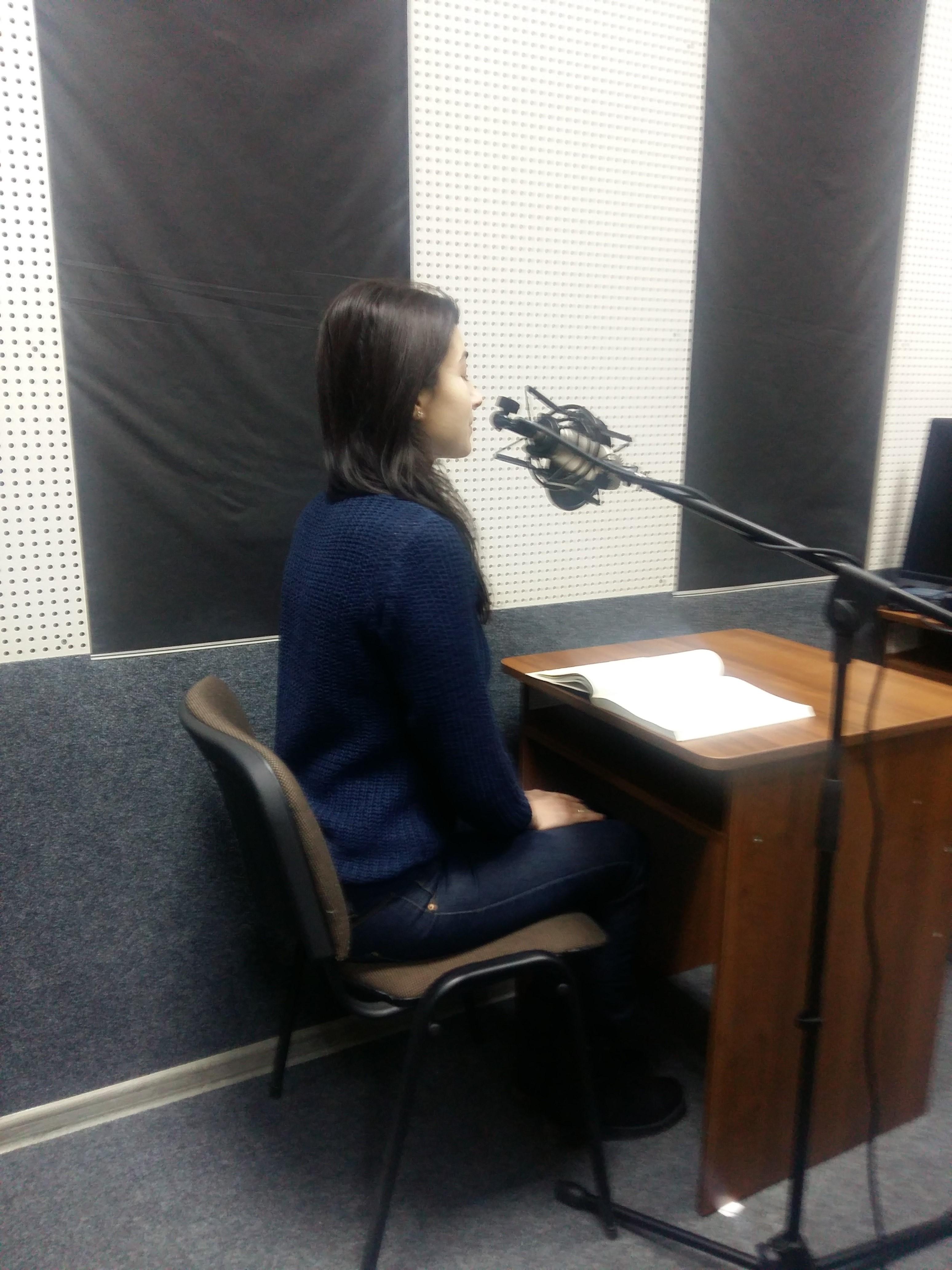Волонтерка в студії звукозапису працює над озвученням книги